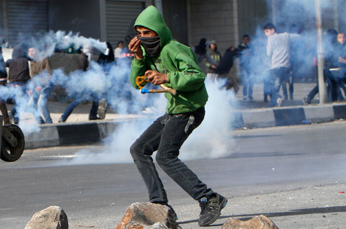 Palestinian protesters run away from tear gas fired by Israeli forces during clashes at Hawara checkpoint near the West Bank city of Nablus March 1, 2013 (Reuters / Abed Omar Qusini)