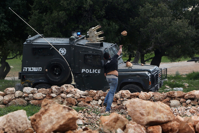 A Palestinian protester throws stones at an Israel border police jeep during a protest marking the 8th anniversary of their campaign against the controversial Israeli barrier in the West Bank village of Bilin near Ramallah March 1, 2013 (Reuters / Mohamad Torokman)