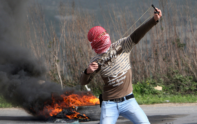 A Palestinian protester uses a sling shot to throw stones towards Israeli forces during clashes at Hawara checkpoint near the West Bank city of Nablus March 1, 2013 (Reuters / Abed Omar Qusini)