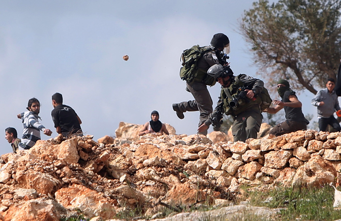 Palestinian protesters throws stones at Israel border policemen during a protest marking the 8th anniversary of their campaign against the controversial Israeli barrier in the West Bank village of Bilin near Ramallah March 1, 2013 (Reuters / Mohamad Torokman)
