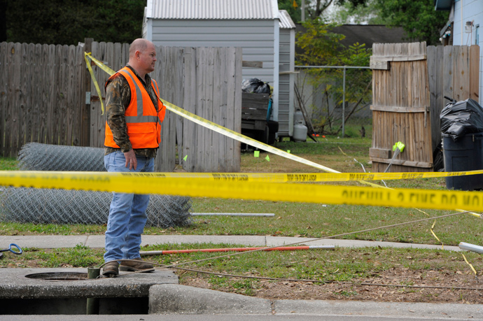 A crew member from the Hillsborough County Public Works Department sends a special pipe camera down a drain within the secured area surrounding a home where a sinkhole opened up and swallowed a man in Seffner, Florida, March 1, 2013 (Reuters / Brian Blanco)