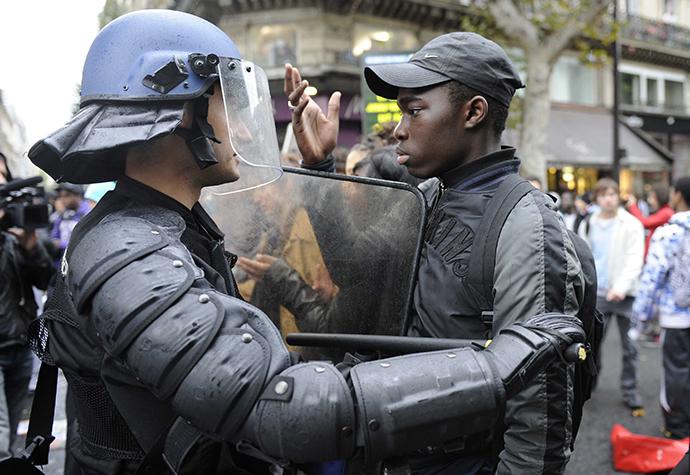 A French high school student faces anti-riot gendarmes during a student demonstration at the Place de la Republique in Paris. (AFP Photo / Gonzalo Fuentes)