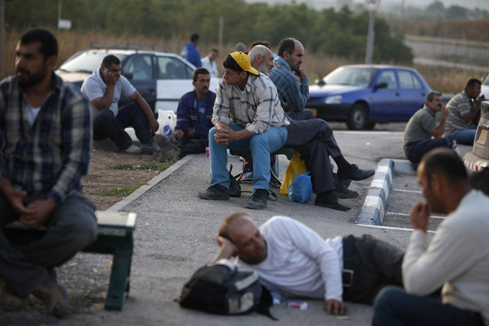 Palestinian labourers wait for work on the side of a road after crossing through Israel's Eyal checkpoint from the West Bank town of Qalqilya (Reuters/Nir Elias)