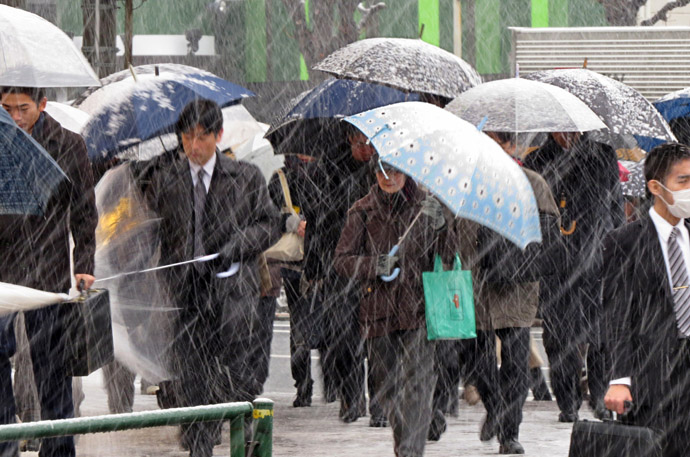 Commuters shelter from the snow under umbrellas whilst on their way to work in Tokyo on February 6, 2013. (AFP Photo/Kazuhiro Nogi)