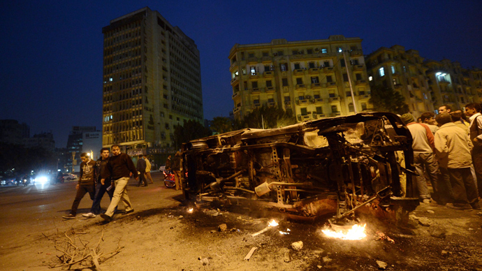 Egyptian look at a police vehicle that has been burnt by angry protesters following clashes with plainclothes policemen in Cairo's on Tahrir square on March 3, 2013 (AFP Photo / Khaled Desouki)