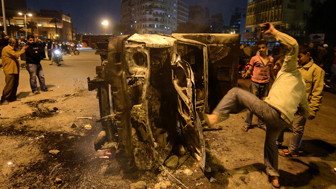 An Egyptian man gives a kick towards a police vehicle that has been burnt by angry protesters following clashes with plainclothes policemen in Cairo's on Tahrir square on March 3, 2013 (AFP Photo / Khaled Desouki)