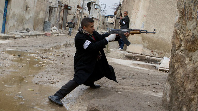 A Syrian rebel aims his weapon during clashes with government forces in the streets near Aleppo international airport in northern Syria on March 4, 2013. (AFP Photo / Stephen J. Boitano)