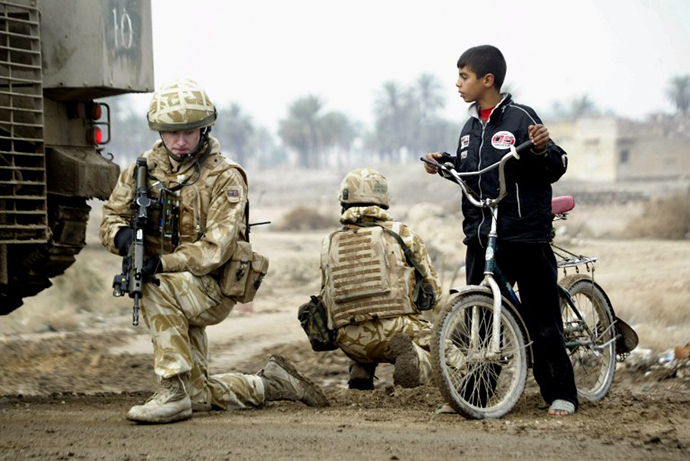 An Iraqi boy stops his bicycle next to British soldiers as they secure the area at the site where a roadside bomb targeted their patrol in the southern city of Basra, 21 January 2007. (AFP Photo / Essam Al-Sudani)