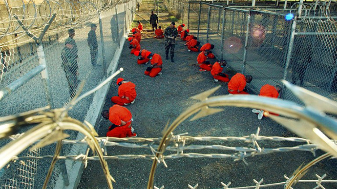 Detainees in orange jumpsuits sit in a holding area under the surveillence of US military police at Camp X-Ray at Naval Base Guantanamo Bay, Cuba. (AFP Photo / Shane T. Mccoy)