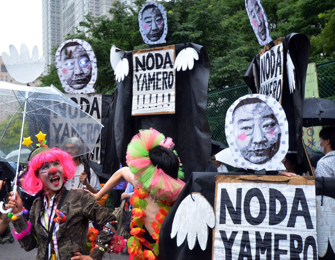 Anti nuclear activists hold placards during a demonstration on a street in Tokyo on July 1, 2012. (AFP Photo / Yoshikazu Tsuno)