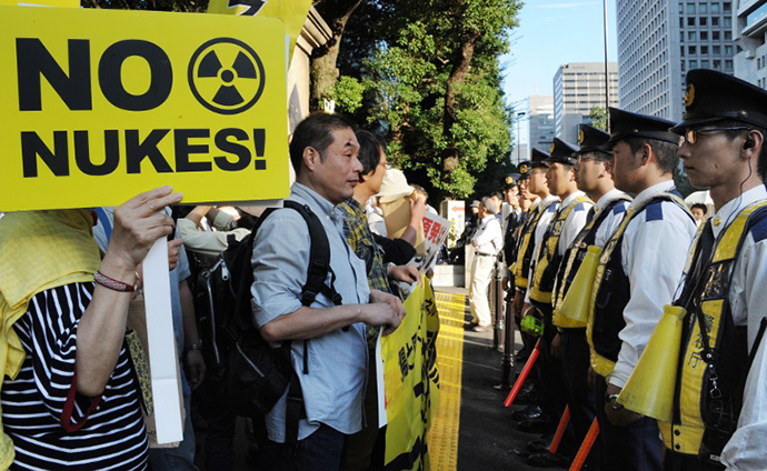 People hold placards in front of policemen during a demonstration in downtown Tokyo on October 13, 2012 denoucing the Japanese government's plan to resume nuclear power use after halting operations after last year's Fukushima crisis. (AFP Photo / Rie Ishii)