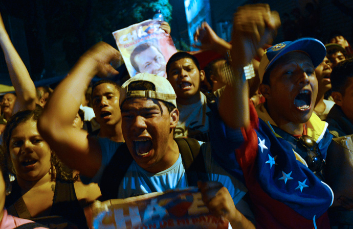 Supporters of Venezuelan President Hugo Chavez shout slogans in front of the Military Hospital, in Caracas on March 5, 2013, after knowing of their leader's death (AFP Photo / Leo Ramirez)