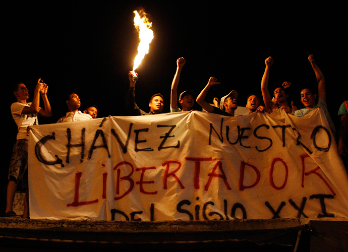 "Supporters of Venezuela's President Hugo Chavez react to the announcement of his death outside the hospital where he was being treated, in Caracas, March 5, 2013. The banner reads, ""Chavez, our liberator in the 21st Century."" (Reuters / Carlos Garcia Rawlins)"