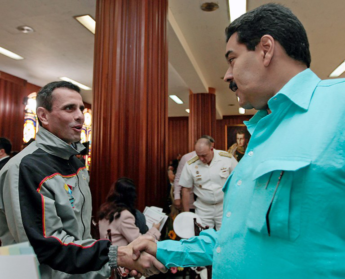 Venezuelan Vice President Nicolas Maduro (R) greeting oppposition leader and governor of the Miranda state Henrique Capriles Radonski (C) during the meeting of the Federal Council of Government, in Caracas on January 15, 2013. (AFP Photo)