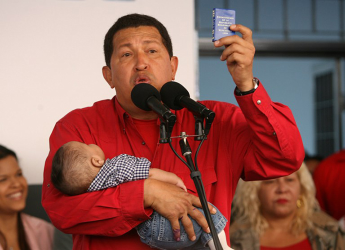 This file picture shows Venezuelan president Hugo Chavez holding his grandson and a copy of the Venezuelan constitution, during a press conference after voting at a polling station 02 December 2007 in Caracas. (AFP Photo / Yuri Cortez)