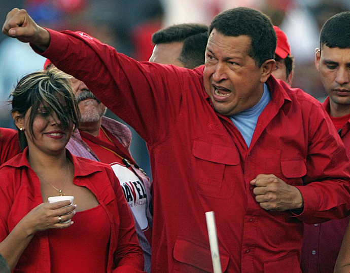 "This file picture shows Venezuelan President and reelection candidate Hugo Chavez gesturing to supporters during a campaign rally at ""Petare"" shantytown in Caracas on November 1, 2006. (AFP Photo / Juan Barreto)"