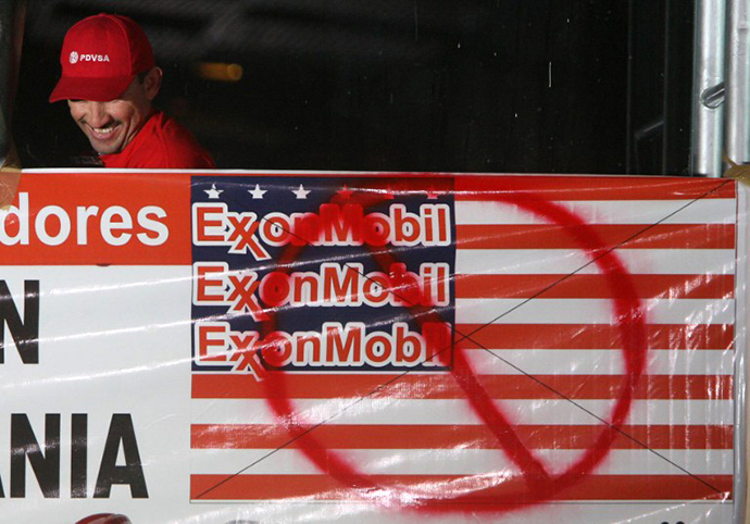 A Petroles de Venezuela (PDVSA) worker smiles next to a banner against ExxonMobil during a meeting to celebrate the court decision against US giant ExxonMobil, at the Simon Bolivar hall in PDVSA's La Campina headquarters in Caracas on March 24, 2008. (AFP Photo / Pedro Rey)