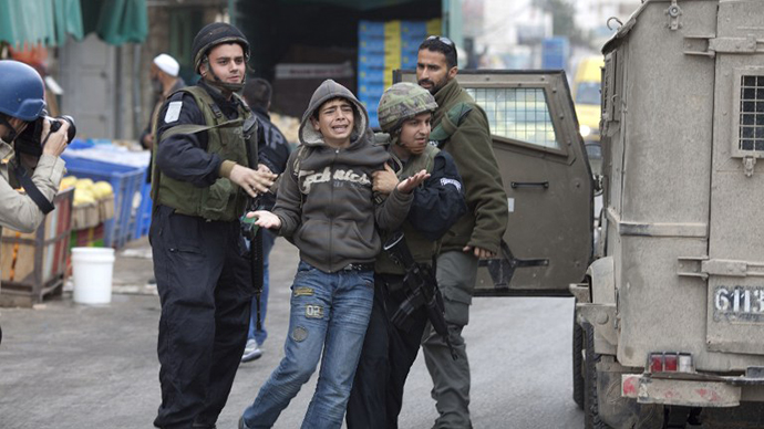 Israeli troops arrest a young Palestinian stone thrower in the West Bank town of Hebron on February 25, 2010. (AFP Photo / Marco Longari)