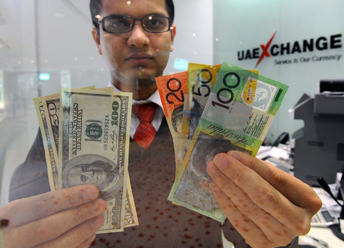 Money changer displays a selection of US dollars and Australian notes. (AFP Photo / Torsten Blackwood)