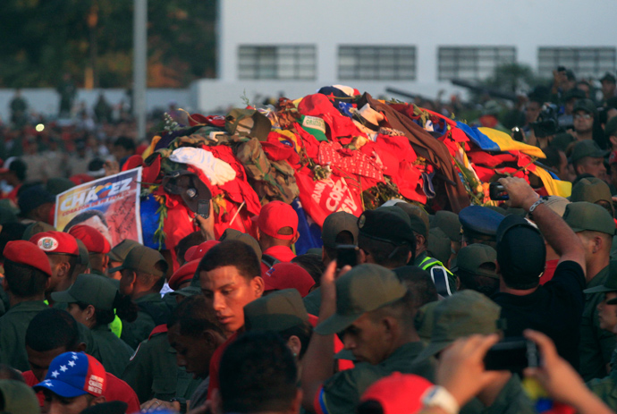 The coffin of late Venezuelan leader Hugo Chavez covered with clothes that people have thrown at it, is driven through the streets of Caracas, after leaving the military hospital where he died of cancer, March 6, 2013 (Reuters / Edwin Montilva)