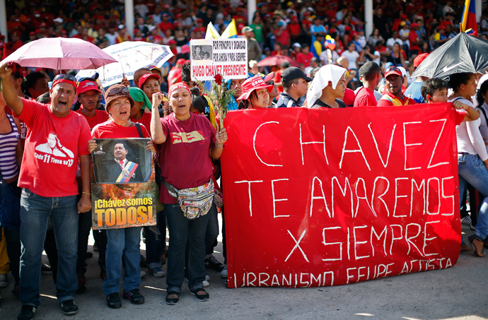 "Supporters of late Venezuelan leader Hugo Chavez watch as his coffin arrives at the Military Academy, where his wake will be held, in Caracas March 6, 2013. The banner reads, ""Chavez, we will love you forever."" (Reuters / Jorge Silva)"