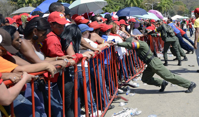 Venezuelan soldiers push the protective fences as supporters wait in line to pay last respects to the late Venezuelan President Hugo Chavez. (AFP Photo / Leo Ramirez)