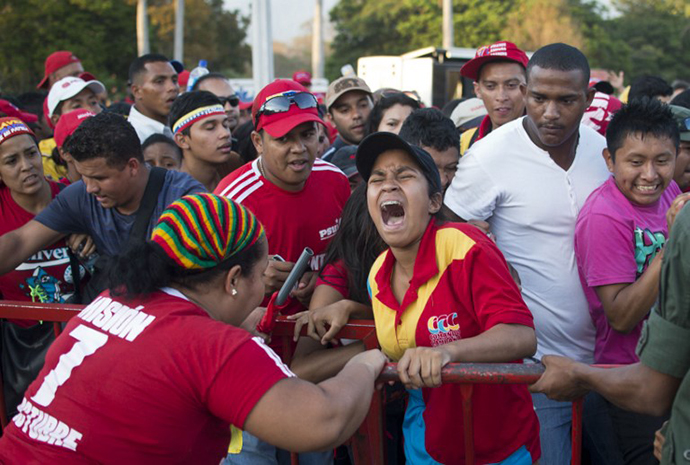 Guards keep supporters behind a fence as they wait to pay respects to late Venezuelan President Hugo Chavez. (AFP Photo / Ronaldo Schemidt)