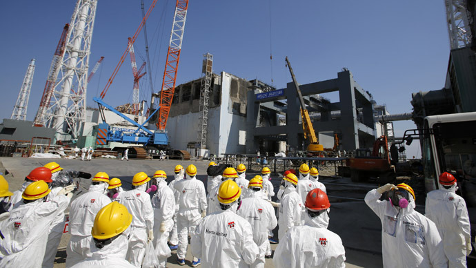 This photo taken on March 6, 2013 shows members of the media wearing protective suits and masks being escorted by Tokyo Electric Power Co (TEPCO) employees as they visit near the No.4 reactor (C) and the construction of a foundation (R) for storage of melted fuel rods at TEPCO's tsunami-crippled Fukushima Dai-ichi nuclear power plant in the town of Okuma, Fukushima prefecture, ahead of the second anniversary of the March 11, 2011 tsunami and earthquake. (AFP Photo/Issei Kato)