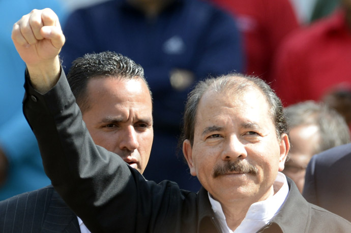 Nicaragua's President Daniel Ortega raises his clenched fist in salutation during the funeral of Venezuela's President Hugo Chavez in Caracas, on March 8, 2013. (AFP Photo/Juan Baretto)