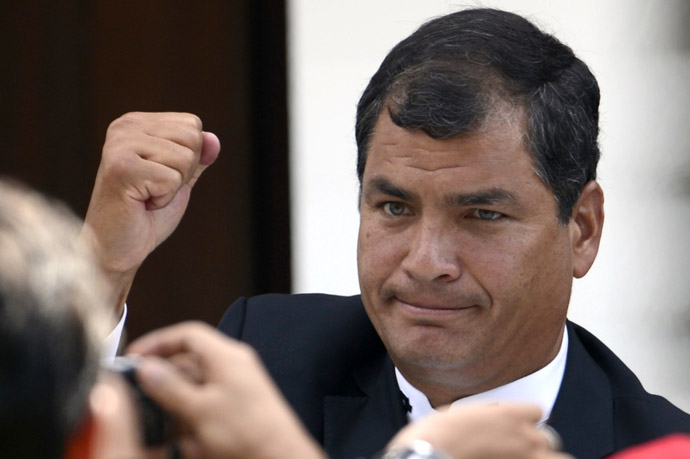 Ecuador's President Rafael Correa raises his clenched fist in salutation during the funeral of Venezuela's President Hugo Chavez in Caracas, on March 8, 2013. (AFP Photo/Juan Barreto)