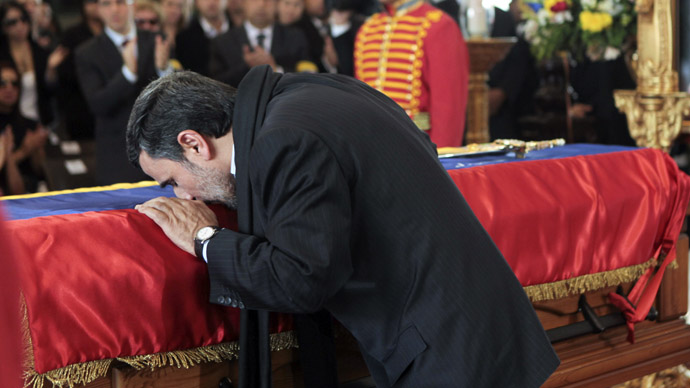 This handout picture released by Venezuelan presidency press office shows Iranian President Mahmoud Ahmadinejad greeting the coffin of late Venezuelan President Hugo Chavez in Caracas, on March 8, 2013. (AFP Photo/Presidencia/Miguel Angel Angulo)