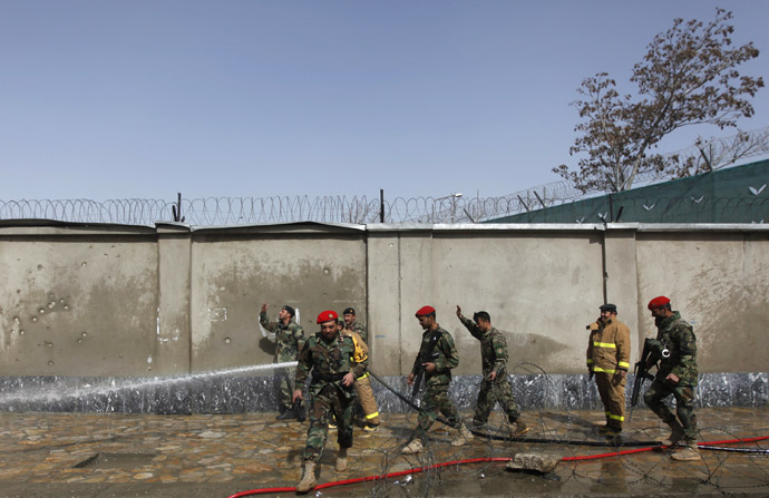Afghan firefighters wash debris off the road at the site of a suicide attack in Kabul March 9, 2013 (Reuters/Mohammad Ismail)