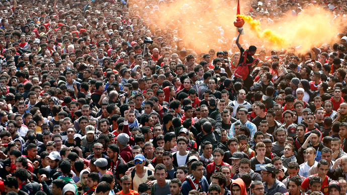 An Egyptian al-Ahly football club supporter (Ultras) lights a flare as they await the verdict of the court over a deadly football riot in Port Said that killed 74 people last year in Cairo on March 9, 2013 (AFP Photo / Mahmud Khaled)