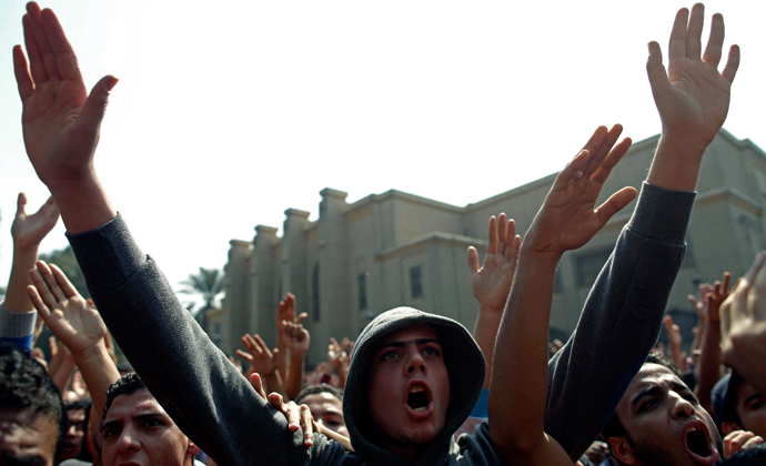 Egyptian al-Ahly football club supporters (Ultras) wave their hands as they celebrate in Cairo on March 9, 2013 (AFP Photo / Mahmud Khaleh)