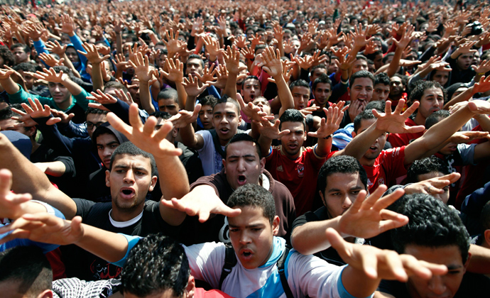 Egyptian al-Ahly football club supporters (Ultras) wave their hands as they celebrate in Cairo on March 9, 2013 (AFP Photo / Mahmud Khaled)