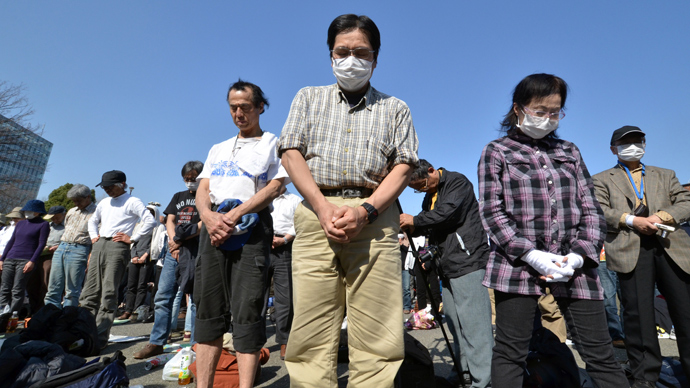 People pray in silence at the start of an anti nuclear rally in Tokyo on March 9, 2013 (AFP Photo / Yoshikazu Tsuno)