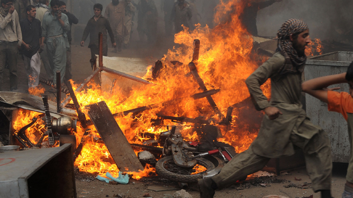 Angry Pakistani demonstrators gather around burning Christian's belongings during a protest over a blasphemy row in a Christian neighborhood in Badami Bagh area of Lahore on March 9, 2013 (AFP Photo / Arif Ali)