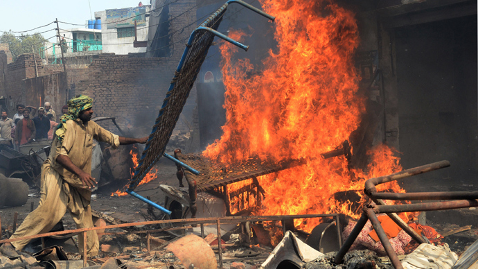 An angry Pakistani demonstrator torches Christian's belongings during a protest over a blasphemy row in a Christian neighborhood in Badami Bagh area of Lahore on March 9, 2013 (AFP Photo / Arif Ali)