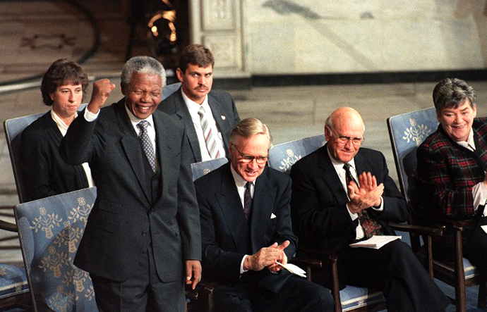 African National Congress President Nelson Mandela (L) salutes a South African choir while the president of the Nobel committee Dr. Francis Sejersted (C) and South African president Frederik De Klerk (R) applaud the choir's performance, 10 December 1993 in Oslo, where both leaders received the 1993 Nobel Peace Prize. (AFP Photo / Gerard Julien)