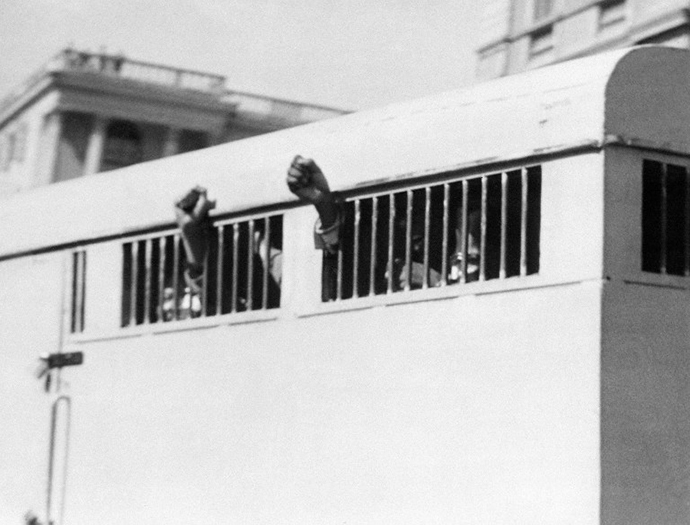 Eight men, among them anti-apartheid leader and African National Congress (ANC) member Nelson Mandela, sentenced to life imprisonment in the Rivonia trial leave the Palace of Justice in Pretoria 16 June 1964 with their fists raised in defiance through the barred windows of the prison car. (AFP Photo)