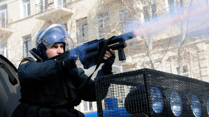 A riot policeman fires tear gas to disperse people during a rally against soldiers death in the national Azerbaijan's army in Baku on March 10, 2013 (AFP Photo / Tofik Babayev)
