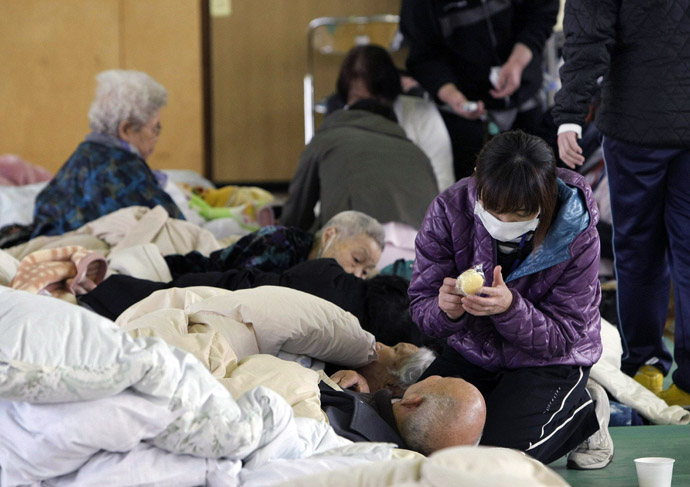 A staff member (R) of a nursing home takes care of elderly people at a shelter in Tamura after they were evacuated from the area near the nuclear plants in Fukushima prefecture on March 13, 2011 two days after a massive 8.9 magnitude quake and tsunami hit the region. (AFP Photo/JiJi Press)