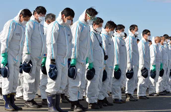 Police officers in radiation protection suits bow their heads to offer prayers in silence for tsunami victims in Namie, near the striken TEPCO's Fukushima Dai-ichi nuclear plant in Fukushima prefecture on March 11, 2013. (AFP Photo/Yoshikazu Tsuno)