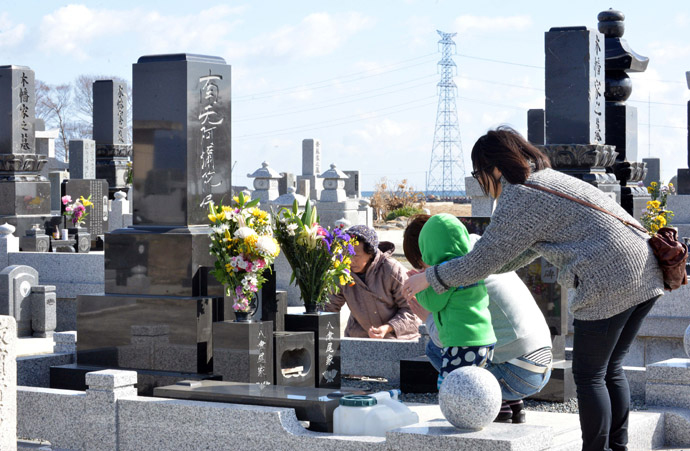 A family prays for their relatives killed by the 2011 tsunami at a cemetery in Minamisoma in Fukushima prefecture on March 11, 2013. (AFP Photo/Yoshikazu Tsuno)