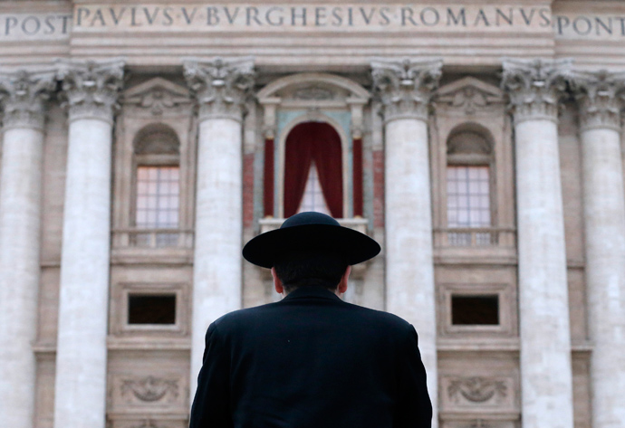 A priest stands in front of Saint Peter's Basilica as a red curtain has been put on the central balcony, called the Loggia of the Blessings, at the Vatican March 11, 2013 (Reuters / Christian Hartmann)