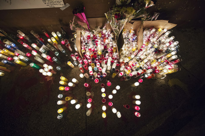 "Candles stand lit on a street corner making up a memorial for 16-year-old Kimani ""Kiki"" Gray, after he was killed in a New York Police Department shooting in the Brooklyn borough of New York, March 11, 2013. (Reuters/Lucas Jackson)"