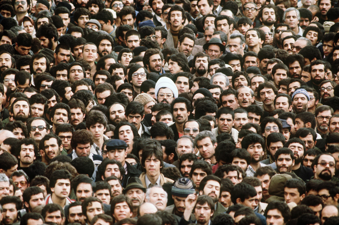A crowd in Tehran walks down a street in February 1979, several days after Ayatollah Khomeini returned from exile. As the uprising gripped the city, protesters wore a shroud or white ribbon around the heads to signify their willingness to die as martyrs. (AFP Photo)