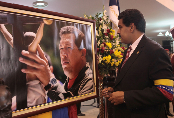 Acting Venezuelan President Nicolas Maduro (R) looks at a photograph of late Venezuelan President Hugo Chavez during the funeral at the military academy in Caracas in this picture provided by Miraflores Palace on March 8, 2013 (Reuters / Miraflores Palace / Handout)