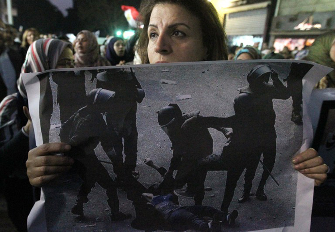 An Egyptian woman holds the widespread picture of a woman who was stripped and beaten by military police during clashes last week as Egyptians gather for a protest in downtown Cairo. (AFP Photo / Khaled Desouki)
