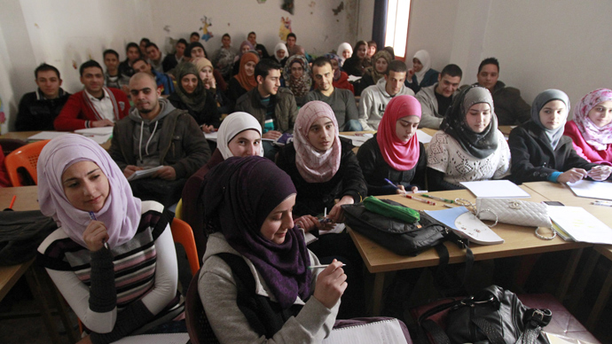 "Palestinian refugees, some of whom fled the Yarmuk refugee camp in Damascus, attend class in the ""Palestine"" Palestinian refugee camp in the Syrian city of Homs (AFP Photo / Anwar Amro)"